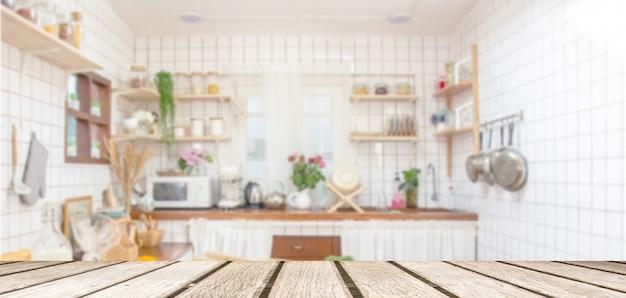 Piano d'appoggio di legno sul fondo della stanza della cucina della sfuocatura. per l'esposizione del prodotto del montaggio o la disposizione visiva chiave di progettazione Foto Premium