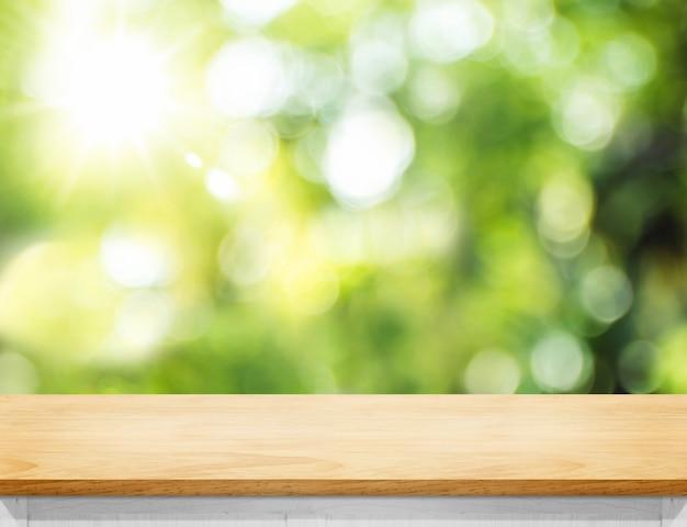 Piano d'appoggio di legno vuoto della plancia con l'albero della sfuocatura in parco Foto Premium