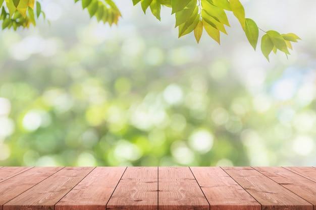 Piano d'appoggio di legno vuoto e vista vaga dal fondo verde del bokeh del giardino dell'albero. Foto Premium
