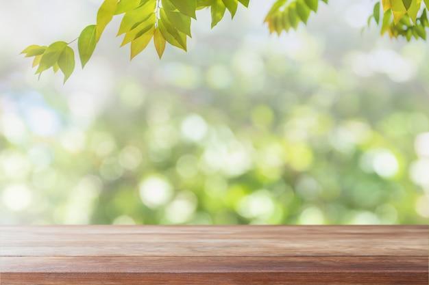 Piano d'appoggio di legno vuoto e vista vaga dal fondo verde del bokeh del giardino dell'albero Foto Premium