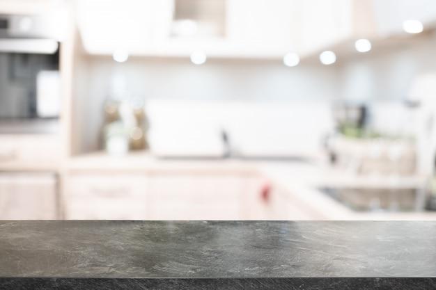 Piano d'appoggio in marmo, spazio scrivania e sfocato del fondo della cucina. può essere utilizzato per il montaggio della visualizzazione del prodotto. presentazione aziendale. Foto Premium