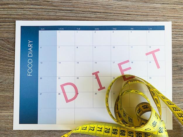 Piano dietetico. nastro di misurazione e piano dietetico su fondo di legno. Foto Premium