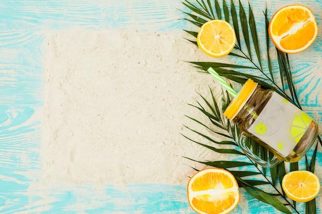 Pianta foglie vicino a bicchiere di bevanda e arance con sabbia a bordo Foto Gratuite