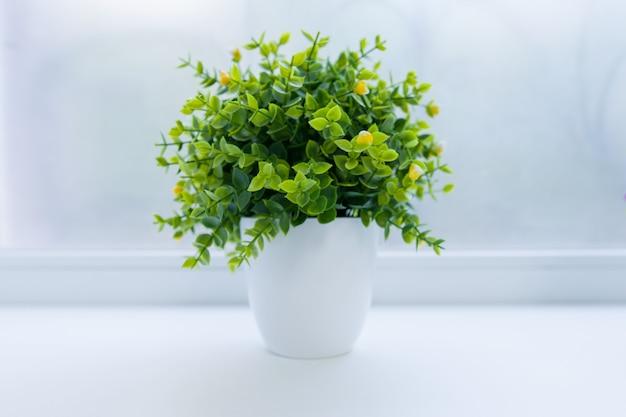 Pianta interna artificiale verde in vaso bianco Foto Premium