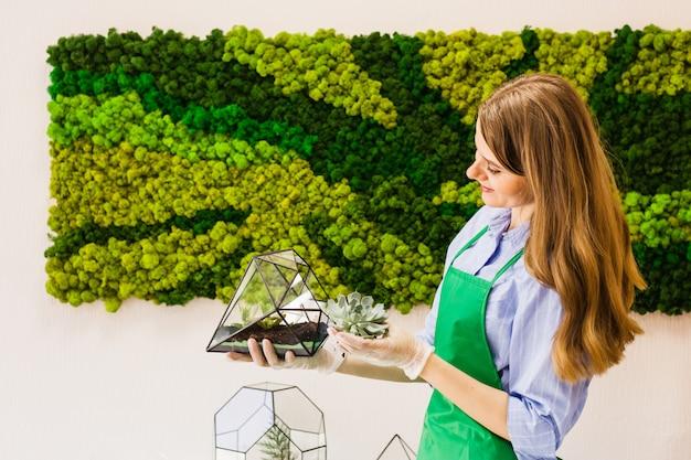 Piante da giardino fiorista ragazza in forma di vetro, sabbia, piante grasse, guanti, muschio, interni Foto Premium