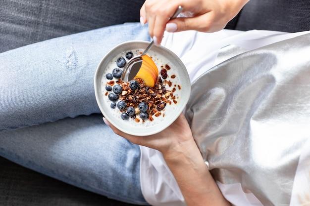 Piastra con muesli e frutti di bosco freschi nelle mani di una giovane ragazza Foto Premium