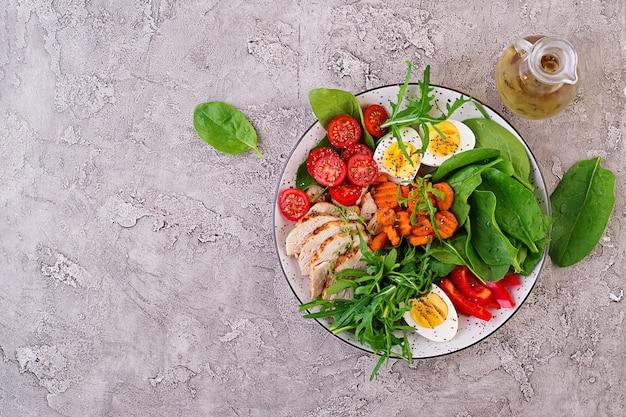 Piastra con un alimento dieta cheto. pomodorini, petto di pollo, uova, carota, insalata con rucola e spinaci. pranzo di keto. vista dall'alto Foto Gratuite