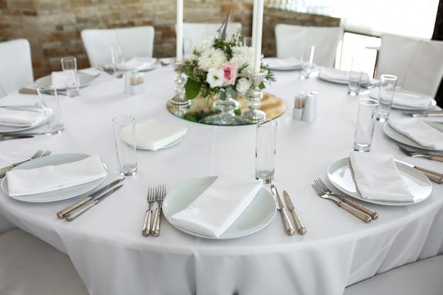 Piatti bianchi, argenteria, tovaglia bianca e stanza bianca. tavolo per banchetti per gli ospiti Foto Premium