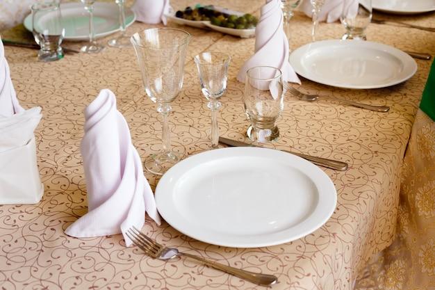 Piatti bianchi vuoti con tovaglioli, bicchieri da vino, forchette, coltelli, primo piano, posate sul tavolo del banchetto nel ristorante Foto Premium
