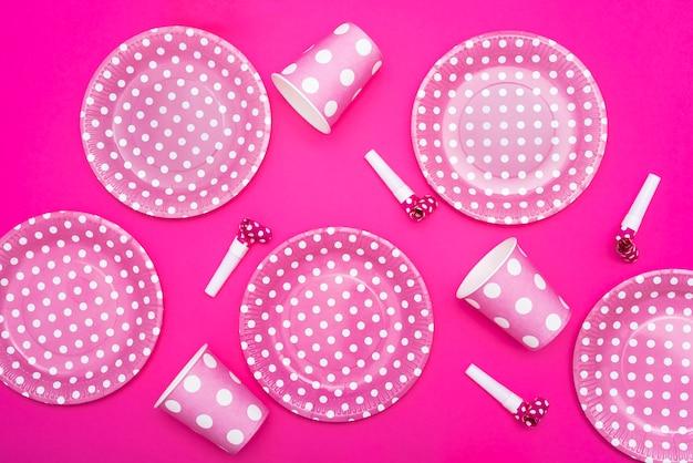Piatti e fischietti punteggiati e tazze su fondo rosa Foto Gratuite
