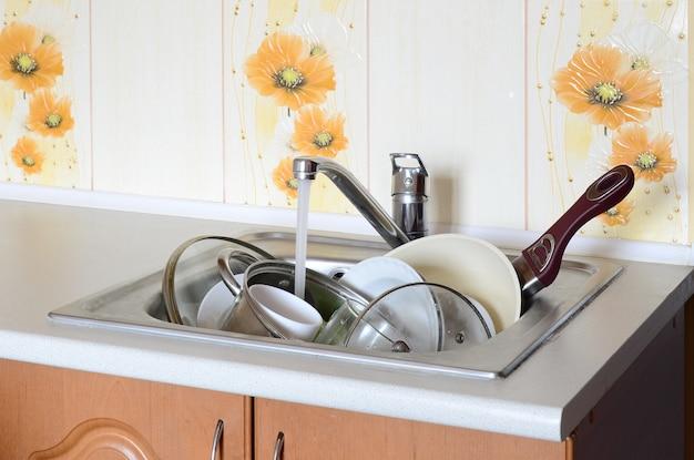 Piatti sporchi e apparecchi da cucina non lavati giacciono nell'acqua schiumosa sotto un rubinetto di un rubinetto della cucina Foto Premium