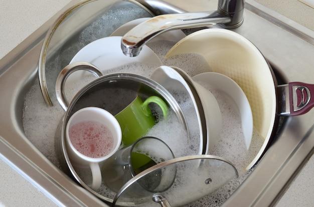 Piatti sporchi e apparecchi da cucina non lavati riempivano il lavello della cucina Foto Premium