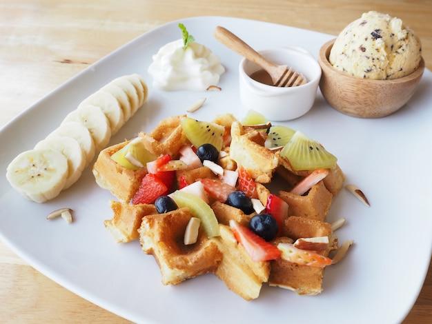 Piatto bianco della cialda con frutta mista e gelato sulla tavola di legno Foto Premium