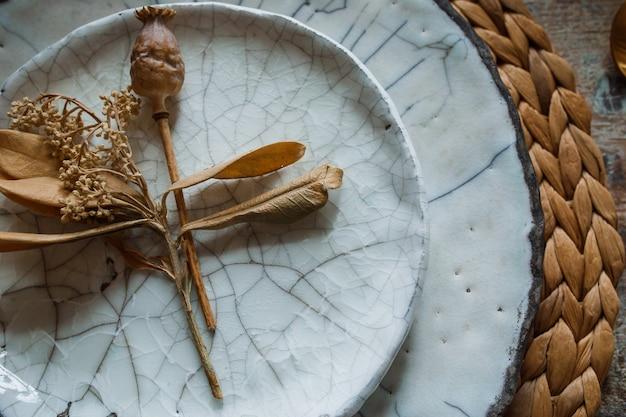 Piatto bianco e forchetta d'oro con un cucchiaio, apparecchi per friggere, decorazione di nozze. Foto Premium