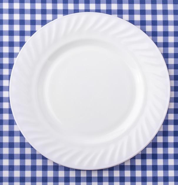 Piatto bianco sul fondo a quadretti blu e bianco della tovaglia del tessuto. Foto Premium