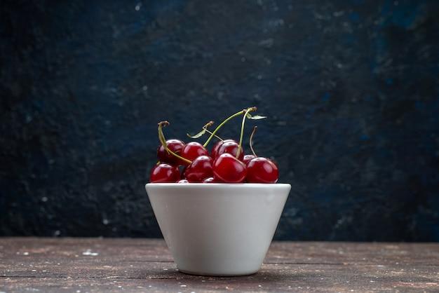 Piatto bianco vista frontale con ciliege fresche rosse aspre sullo scrittorio di legno marrone Foto Gratuite
