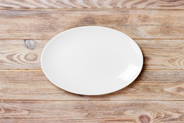 Piatto bianco vuoto sulla tavola di legno. vista dall'alto Foto Premium