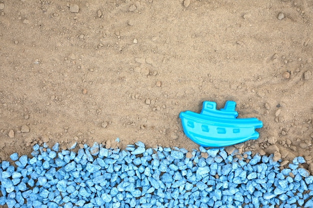 Piatto ciottoli blu con barca sulla sabbia Foto Gratuite