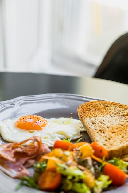 Piatto colazione grigio con uovo; bacon; pane tostato e insalata sul tavolo Foto Gratuite
