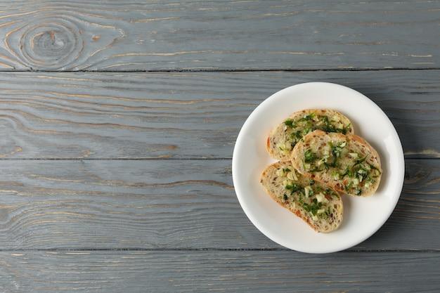 Piatto con pane all'aglio tostato su fondo di legno, vista superiore Foto Premium