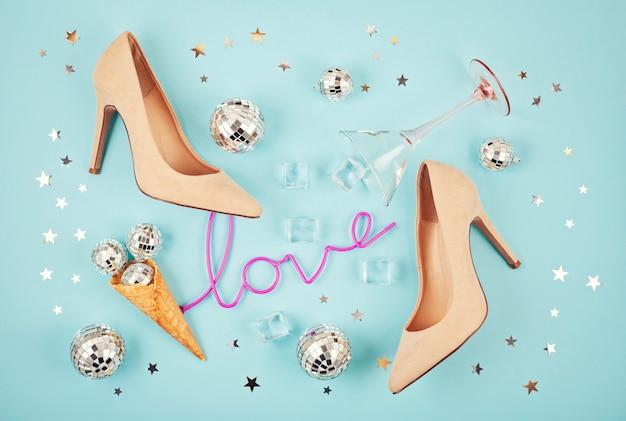 Piatto con scarpe da donna, palle da discoteca, cubetti di ghiaccio, bicchiere da cocktail e confetti. Foto Premium