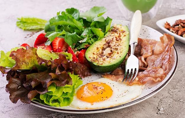 Piatto con una dieta cheto, uova fritte, pancetta, avocado, rucola e fragole, colazione keto. Foto Premium