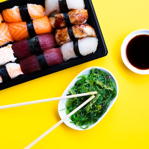 Piatto del contenitore di sushi con l'insalata dell'alga e la salsa di soia su fondo giallo Foto Gratuite