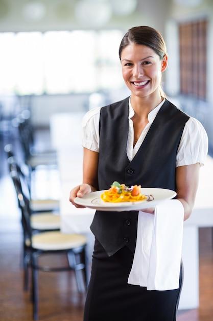 Piatto della tenuta della cameriera di bar in un ristorante Foto Premium