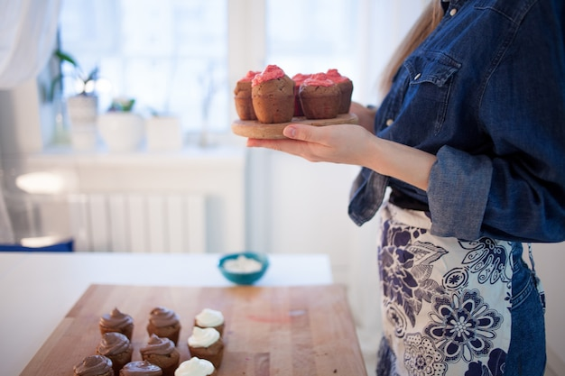 Piatto della tenuta della ragazza dei muffin caldi freschi, vago Foto Premium