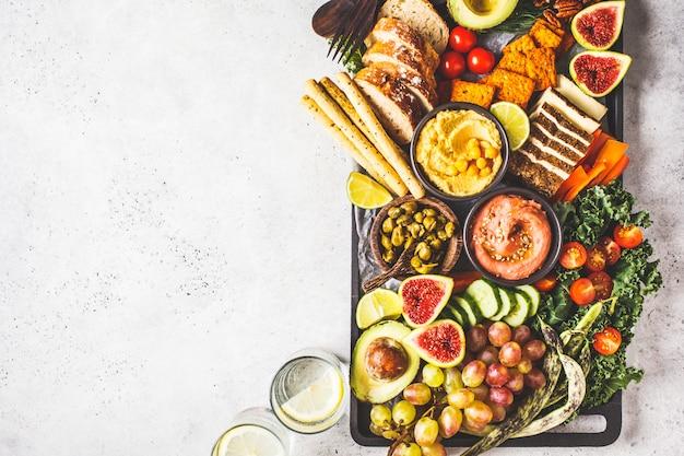 Piatto di antipasti vegani, hummus, tofu, verdure, frutta e pane Foto Premium