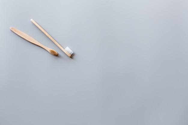 Piatto di bambù naturale eco spazzolini da denti giaceva su sfondo grigio Foto Premium