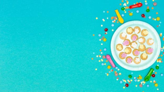 Piatto di biscotti circondato da palloncini e coriandoli Foto Gratuite