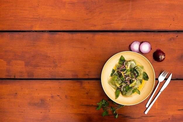 Piatto di contorno di ravioli verdi pasta con cipolla sul tavolo di legno Foto Gratuite