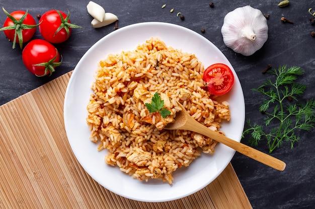 Piatto di delizioso pilaf fatto in casa con pollo, prezzemolo fresco e verdure mature per il pranzo Foto Premium