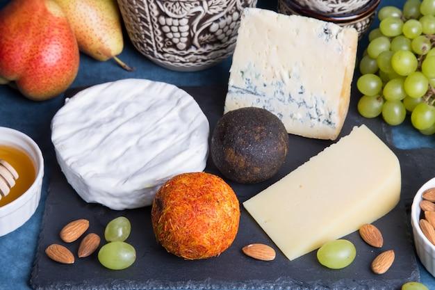 Piatto di formaggi. 5 specie di formaggio, frutta, noci, caraffa di vino. primo piano, messa a fuoco selettiva. Foto Premium