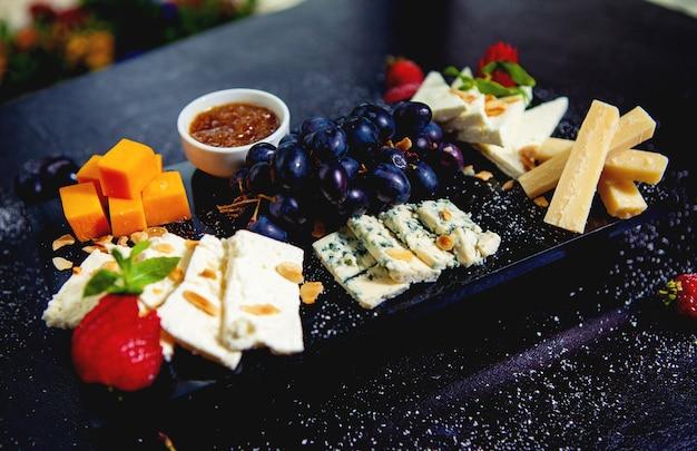 Piatto di formaggi con cubetti di formaggio cheddar, formaggio bianco, bastoncini di parmigiano, gorgonzola e uva Foto Gratuite