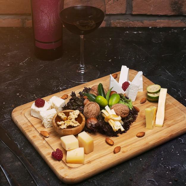 Piatto di formaggi con diversi formaggi, uva, noci, miele, pane e datteri su legno rustico. su tavola di legno scuro con bottiglia di vino e bicchiere di vino Foto Gratuite