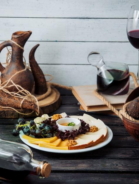 Piatto di formaggi con formaggio cheddar, affumicato, bianco, noci, uva e miele Foto Gratuite