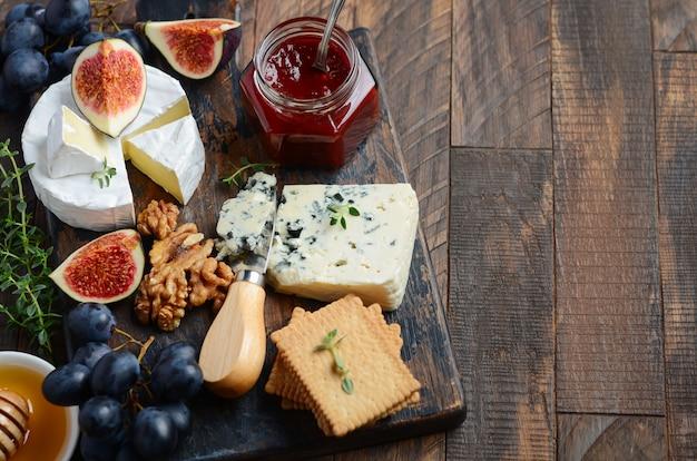 Piatto di formaggi con uva, fichi, cracker, miele, gelatina di prugne, timo e noci. Foto Premium