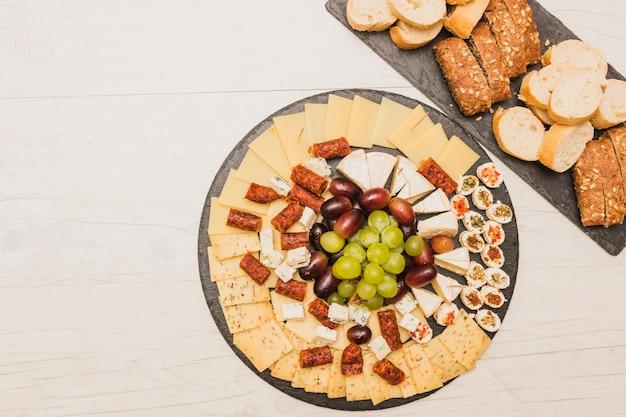 Piatto di formaggi con uva; salsicce affumicate e pane Foto Gratuite