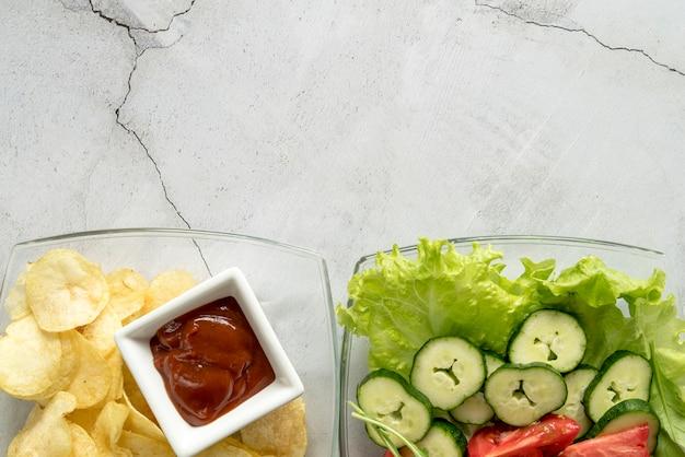 Piatto di insalata di verdure organiche e patatine con salsa di pomodoro su sfondo concreto Foto Gratuite