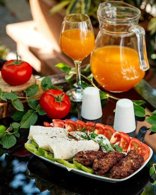 Piatto di kebab con pomodoro, peperone, focaccia e cipolla Foto Gratuite