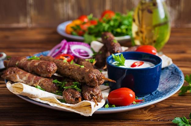 Piatto di kebab tradizionale turco e arabo ramadan mix. kebab adana, pollo, agnello e manzo su pane lavash con salsa. vista dall'alto Foto Gratuite