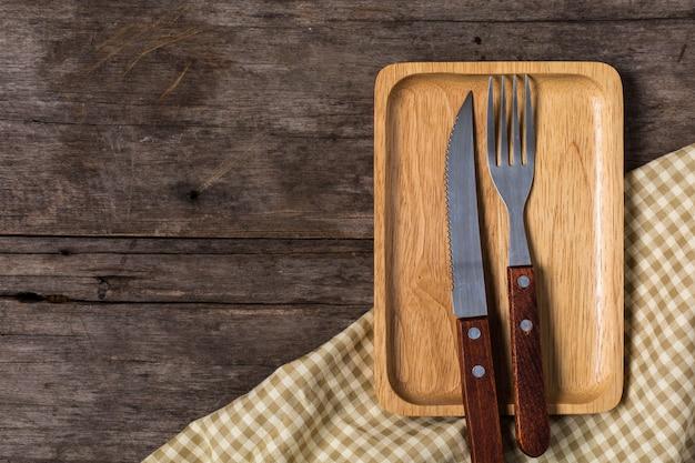 Piatto di legno con il coltello da bistecca su fondo di legno Foto Premium