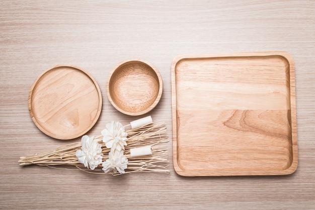 Piatto di legno con il fiore secco sui precedenti di legno. Foto Premium