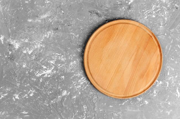 Piatto di legno sui precedenti strutturati grigi. vista dall'alto Foto Premium