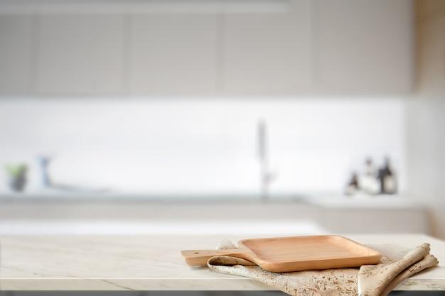 Piatto di legno sulla tavola bianca nel fondo della stanza della cucina e spazio della copia per il montaggio dell'alimento o del prodotto Foto Premium