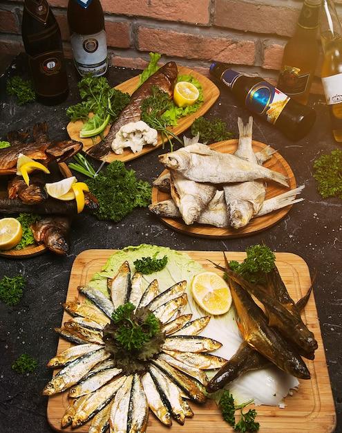 Piatto di pesce che cucina con vari ingredienti e tipi di pesce. branzino crudo con limone, aglio, erbe e spezie sul tagliere. cibo sano o concetto di nutrizione dieta. Foto Gratuite