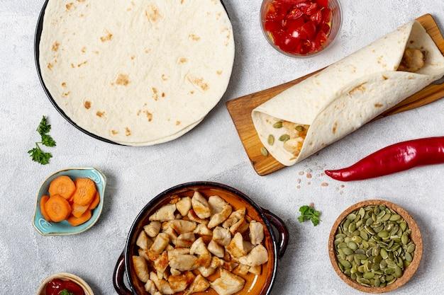 Piatto di pollo, burrito e tortilla vicino alle verdure sulla tavola Foto Gratuite