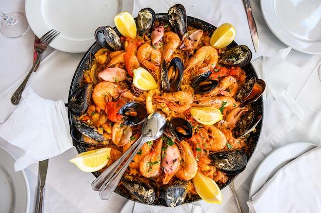 Piatto di riso alla paella di pesce spagnolo con gamberi freschi, scampi, cozze, calamari, polpi e capesante servito in padella. vista dall'alto. ristorante Foto Premium